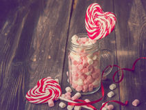 Sweets for Valentines Day. Heart shaped lollipos and the jar with marshmallows for Valentines Day on the old wooden background. Vintage toned picture Stock Images