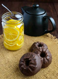 Sweets: Zephyr in chocolate and tea with lemon on wooden background. Stock Images