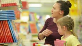 Sweetydotter som visar till hennes moder en bok En dotter önskar att köpa denna bok med illustrationer De har mycket stock video
