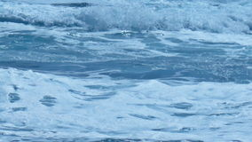 Swelling Foamy Waves Splash in Turquoise Sea Water. Static medium long close up shallow depth of field shot of swelling waves rolling over and splashing on fresh stock video footage