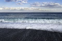 Swells crashing into black pebbled beach in Sicily. Swells crashing into black pebbled beach Giardini di Naxos in Sicily on a blue sky windy summer day stock images