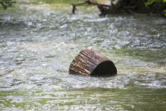 Swept up. A log is swept up by a river in Ohio.  The river carries it downstream to unknown places Stock Photography