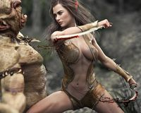 Swift Female Wood Elf Warrior Making Quick Work Of An Attacking Troll. Stock Photography