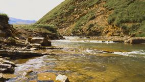 Swift mountain river flows through a highland valley in Caucasus mountains stock video footage