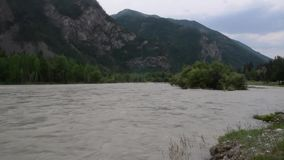 Swift water flow in mountain river, rocks along the river bank stock video footage
