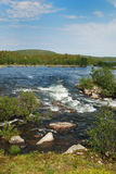 Swift wide river in the Finnish taiga forest. Royalty Free Stock Photography