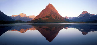 Swiftcurrent Lake Reflection. The Rocky Mountain Peaks of Montana's Glacier National Park reflecting in Swiftcurrent Lake royalty free stock images
