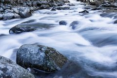 Swiftly moving river water over and around large rocks winter landscape. Horizontal aspect Stock Photos