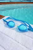 Swiimng goggles on a poolside Stock Photos