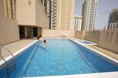 Swim человека в плавательном бассеине на крыше, Бахрейне стоковое изображение rf