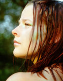 After the swim. A young woman with wet red hair looking into the evening sun after a swim Royalty Free Stock Photo