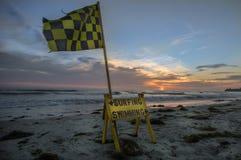 Swim area flag at sunset Stock Photos