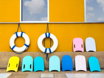 Swim boards and lifebuoy. Colourful swim boards and an old lifebuoy hanging on wall Royalty Free Stock Image