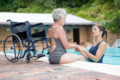 Swim coach consoling a disabled senior woman. At poolside royalty free stock images
