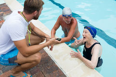 Swim coach interacting with senior couple Stock Image