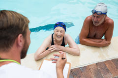 Swim coach interacting with senior couple Royalty Free Stock Photography