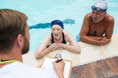 Swim coach interacting with senior couple Stock Photography