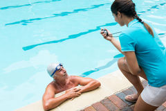 Swim coach interacting with senior man. At poolside Royalty Free Stock Image