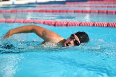 Free Swim Competition Swimmer Athlete Doing Crawl Stroke In Swimming Pool. Sports Man Male Swimmer With Goggles And Cap Royalty Free Stock Image - 191864006