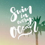 Swim in every ocean. Inspirational quote about travel at filtered background with palm tree. Stock Photos
