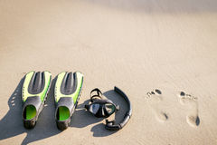Swim flippers with snorkel, mask and feet steps on a sandy beach. Water sports. Snorkeling. Travel and holiday concept. Fins and s Stock Photos