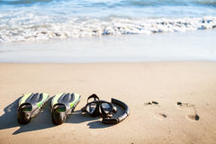 Swim flippers with snorkel, mask and feet steps on a sandy beach. Water sports. Snorkeling. Travel and holiday concept. Fins and s Royalty Free Stock Photo