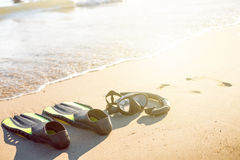 Swim flippers with snorkel, mask and feet steps on a sandy beach. Water sports. Snorkeling. Travel and holiday concept. Fins and s royalty free stock photos