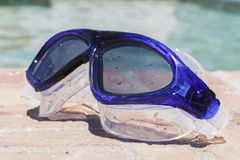 Swim goggles on the edge of a swimming pool Stock Photos