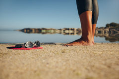 Swim goggles on the sand with a woman standing by. Swim goggles on the sand with feet of a woman standing by. Focus on goggles Royalty Free Stock Images