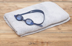 Swim goggles on towel. Over wood background Stock Images