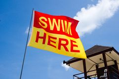 Swim Here Flag Next to Lifeguard House Stock Photos