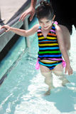 Swim lesson. A 3 year old girl learning how to swim in a swimming class Stock Photography