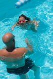 Swim Lesson. Father teaching five year old daughter how to swim in crystal clear blue pool Royalty Free Stock Photos