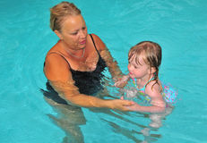 Swim Lesson with Grandma. A grandmother and her granddaughter work on their swimming in the pool Royalty Free Stock Photo