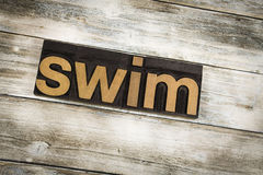 Swim Letterpress Word on Wooden Background Stock Images