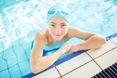 Swim practice. Handsome guy in swim-cap looking at camera out of water while practicing swimming Stock Image