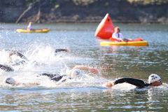 Swim race triathlon. The start of a triathlon swim with a racer forward and in the lead stock image