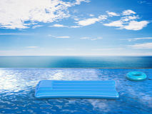 Swim ring and raft on infinity pool. With blue sea and blue sky Royalty Free Stock Photos