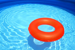 Swim ring in a swimming pool. A bright orange swim ring, floating on a sparkling blue swimming pool Royalty Free Stock Photo