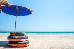 Swim ring with umbrella on the beach Stock Photos