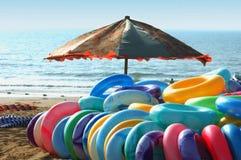 Swim rings and umbrella. On the beach stock photos