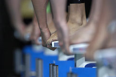 Swim Start 01. Toes and hands touch the blocks at the start of a swim race Stock Image