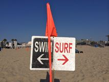 Swim and surf. Hermosa Beach in LA, Yin and yang sign on the beach: swimmers to the right, surfers to the left Royalty Free Stock Image