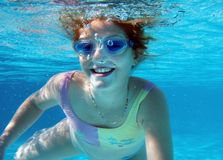 Swim underwater. 8 y.o. happy girl swimming in a pool Stock Photo