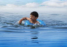 Swiming boy. 9 year old boy swiming in blue water, expressing happyness Royalty Free Stock Photography