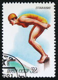 Swiming, circa 1981. MOSCOW, RUSSIA - JANUARY 7, 2017: A stamp printed in the USSR shows a woman jumps into the water, the series `Sport`, Swiming, circa 1981 Stock Photos