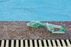 Swiming glasses beside a pool. A fasion swiming glasses beside a sand stone aound the pool Royalty Free Stock Photo