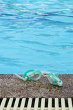 Swiming glasses beside a pool. A swiming glasses place on the floor beside a pool Stock Images