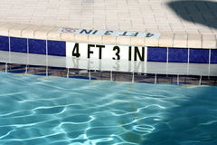 Swiming pool. Depth marked at 4 ft 3 in with blue Stock Photography