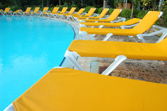 Swiming pool. Seventeen swimming pool chairs along swimming pool Stock Photo